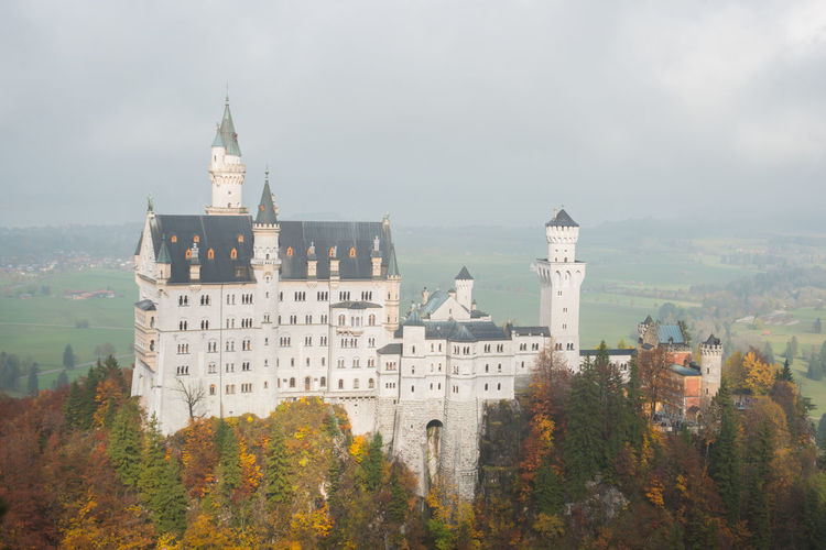 Neuschwanstein Castle with Autumn colors, Fussen, German Architecture Built Structure Building Exterior Nature Tree Sky Building Plant Tower No People Autumn Travel Destinations History Day The Past Travel Religion Cloud - Sky Mountain Outdoors Change
