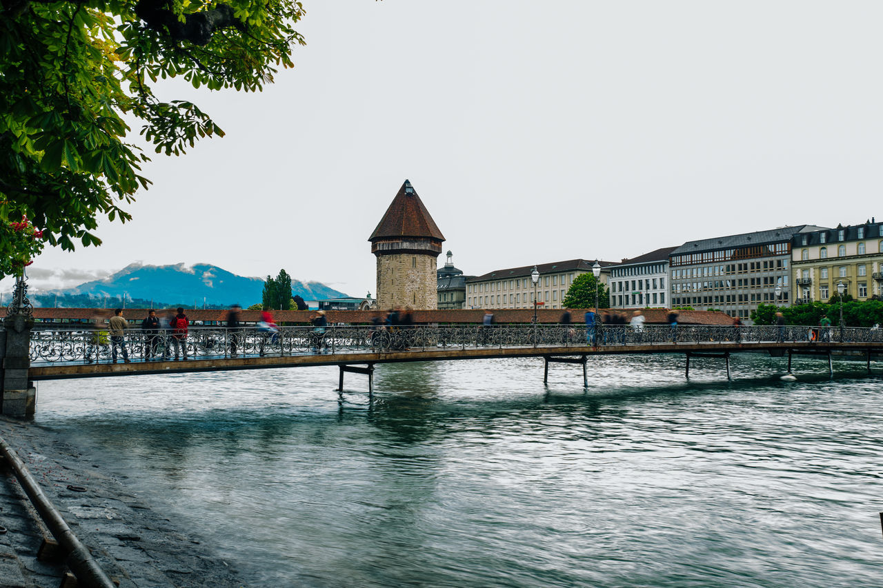 People Walking On Footbridge Against Chapel Bridge Over Reuss River In City