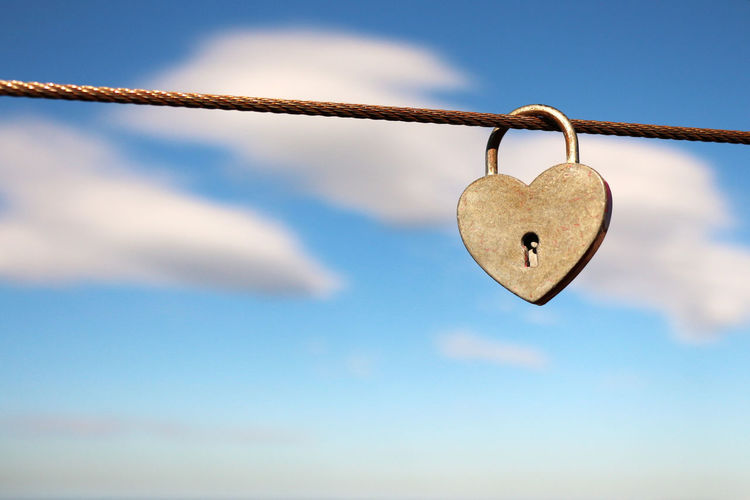 Close-Up Of Heart Shape Padlock On Cable Against Sky