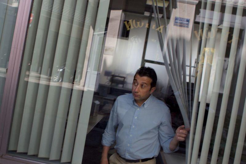 A Greek bank employee peeks out at the street. Bank Candid Streetphotography Man Greece Athens Peekaboo