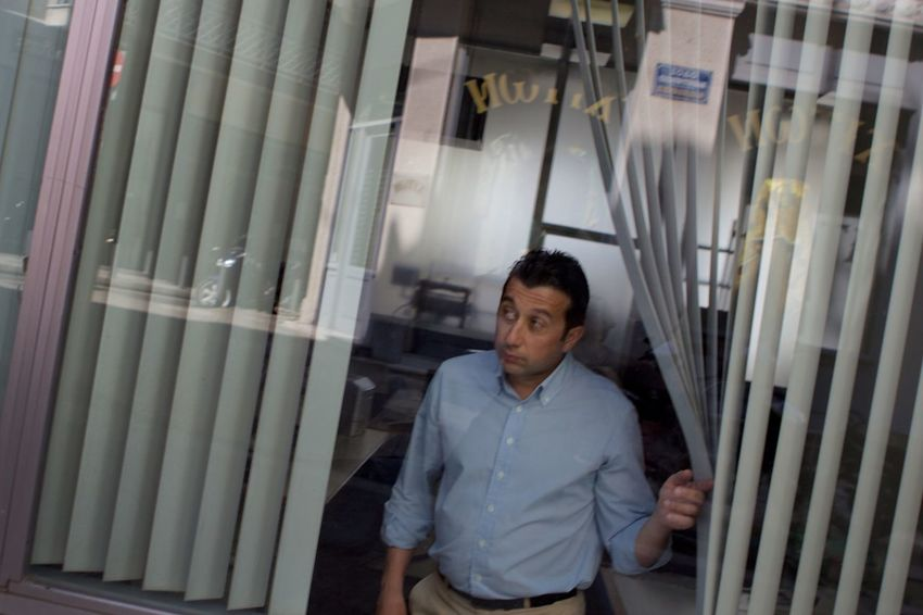 A Greek bank employee peeks out at the street. Bank Candid Streetphotography Man Greece Athens Peekaboo
