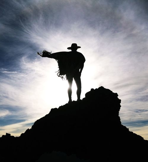 Silhouette Of Man On Mountain Against Dramatic Sky