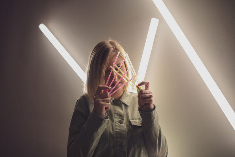 Woman holding colorful equipment against illuminated light