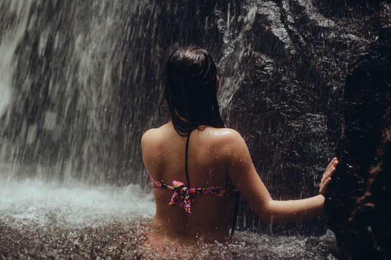 Rear View Of Sensuous Young Woman Standing In River Against Waterfall