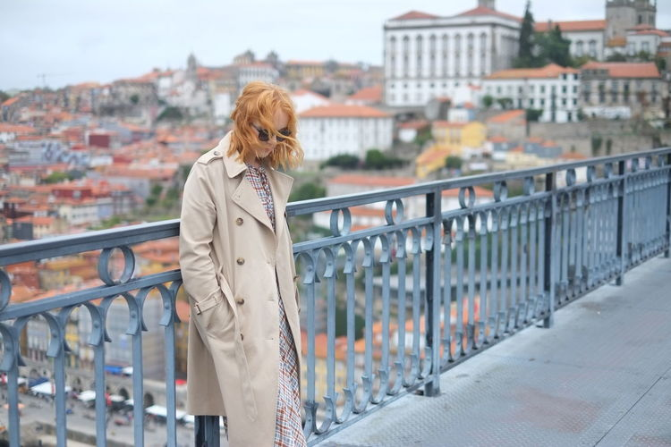 Thoughtful Woman Standing By Railing On Bridge In City