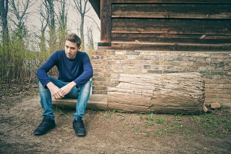 Portrait Of Young Man Sitting On Wood
