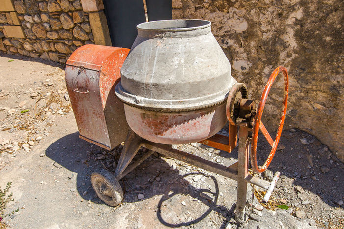Red and grey cement mixer during a house renovation. Bricks and contraction materials during an old house renovation Brick Wall Construction Restoration Work Working Camping Stove Contruction Contruction Zone Day No People Outdoors Rusty