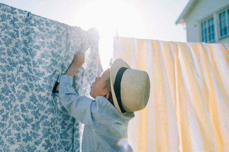 Midsection of man wearing hat standing against curtain