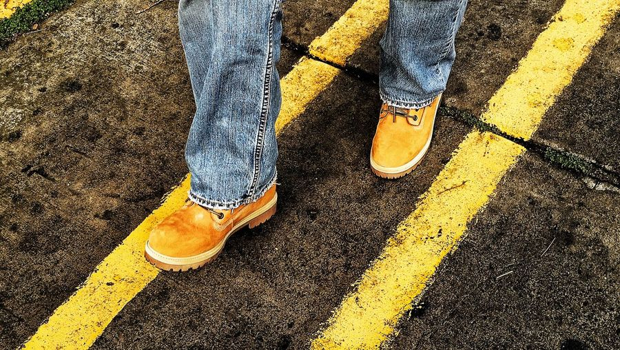 Low section view of man walking between yellow lines