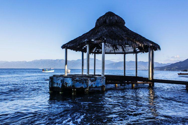 Gazebo in sea against clear blue sky