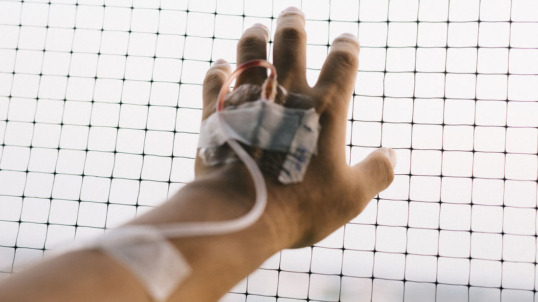 Patient's hand with IV hose grabbing net Asylum Blood Escaping Healthcare Hospital Human Body Part Iv Hose Medicine Mesh Net One Person Patient People Prison Stress