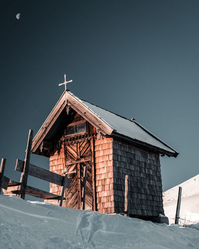 Low angle view of house on snow covered field against sky