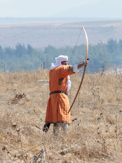 Tiberias, Israel, July 01, 2017 : Participant in the reconstruction of Horns of Hattin battle in 1187 dressed in the suits of an archer of a Muslim army, shoots an onion on the battlefield near Tiberias, Israel Battle Cross Crusaders Field Fire Guy De Lusignan Hattin Heat Heritage History Horn Horseman Infantry Israel Jerusalem KINGDOM Knight  Muslims Palestine Religion Saladin Templars Victory War Weapons