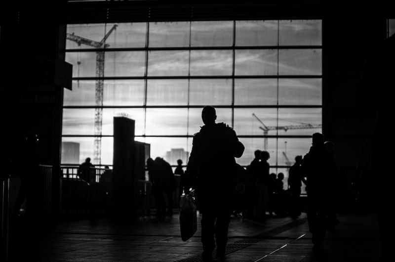 Silhouette people in railroad station against sky during sunset