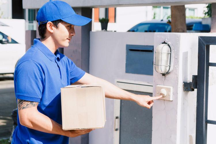 Salesman ringing doorbell while standing at gate way