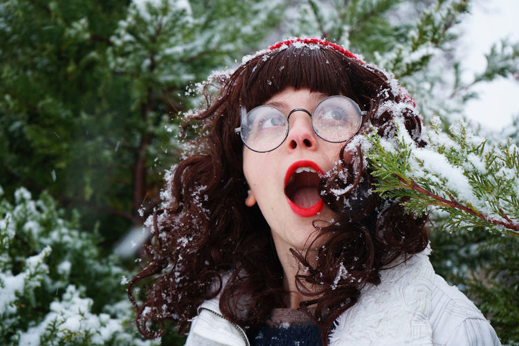 Close-Up Of Young Woman With Mouth Open Against Trees During Winter