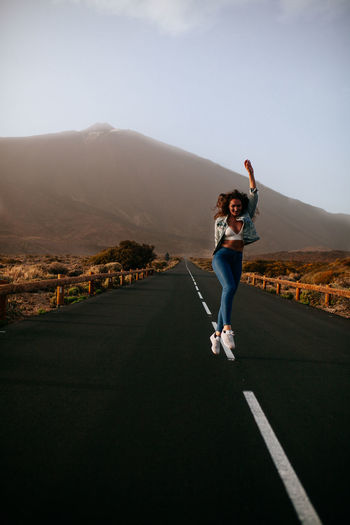 Full Length Of Happy Woman Walking On Road Against Sky