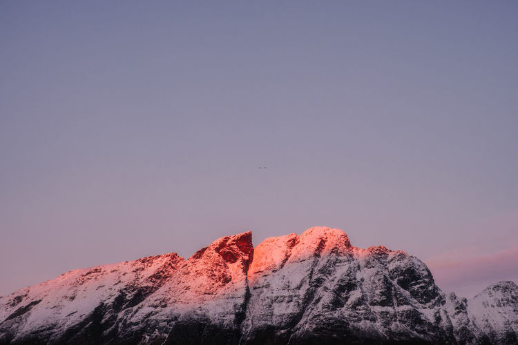 Snowcapped mountain against clear sky during winter
