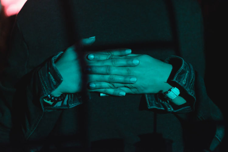 Midsection of woman with interlocked hands at night