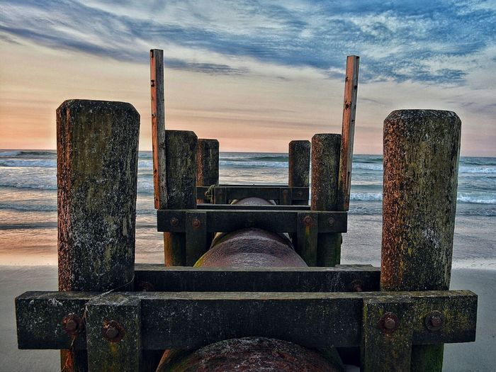 Abandoned Pier At Beach Against Sky