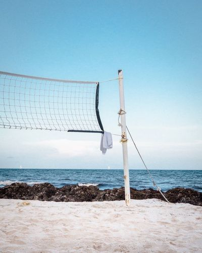 Net at beach against sky during sunny day