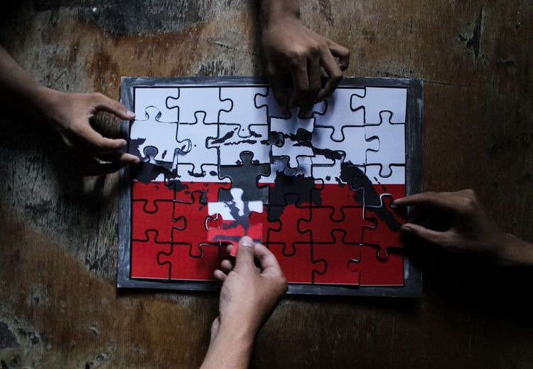 Cropped Hands Of People Playing With Jigsaw Puzzle On Table