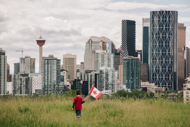 Young boy holding a canadian flag walking in a field with calgary downtown in the background