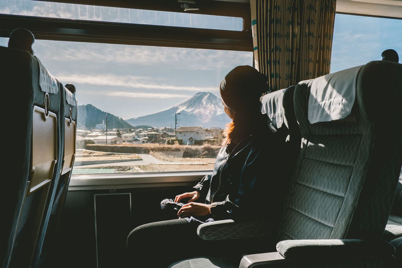 Side View Of Woman Sitting In Bus Against Sky