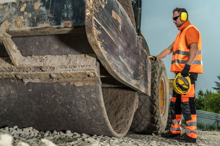 Worker standing by bulldozer at construction site