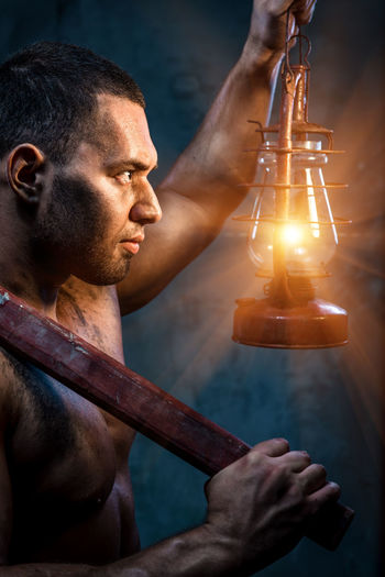 Muscular man holding pickaxe and oil lamp Athlete Athletic Flame Light Man Masculinity Rustic Dirty Hammer Illumination Kerosene Lamp Lighting Miner Muscular Build Night Oil Lamp Old One Person Pickaxe Pitman Source Sportive Strength Strong Tool