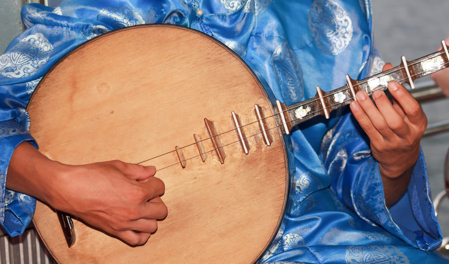 Midsection of person playing traditional guitar
