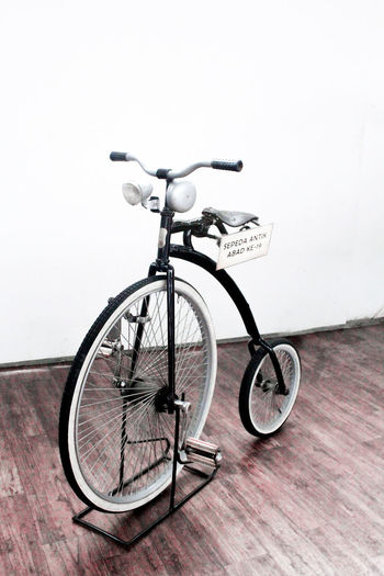 Close-up of bicycle leaning against wall
