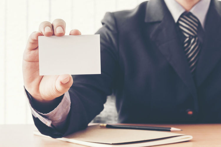 Midsection Of Businessman Holding Blank Card