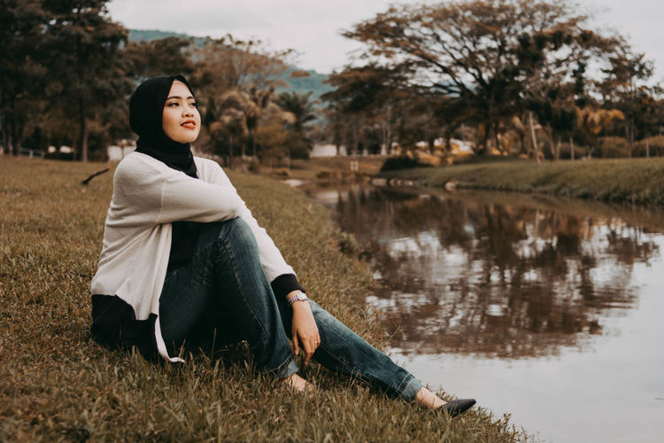 Young woman looking away while sitting by lake against trees