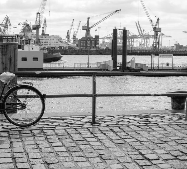Bicycle parked on bridge against cranes at harbor