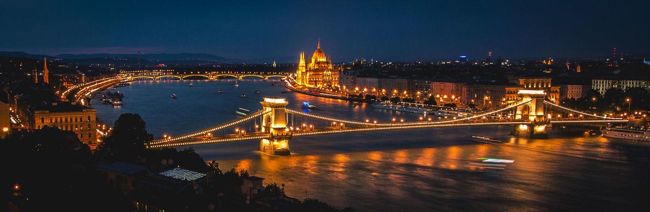 Suspension Bridge Over River At Night