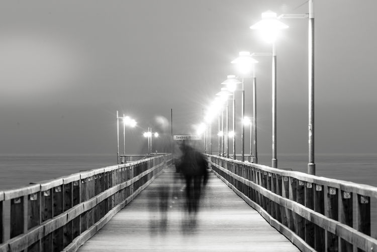 Double Exposure Of People Walking On Illuminated Pier At Night