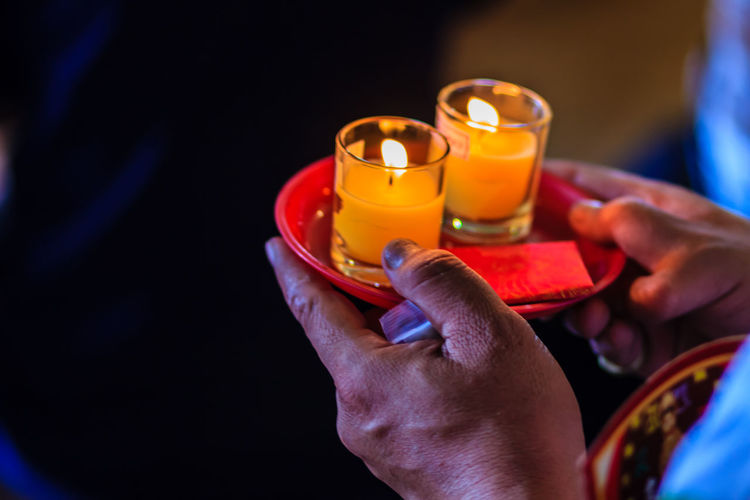 Close-up of hands holding candles in plate