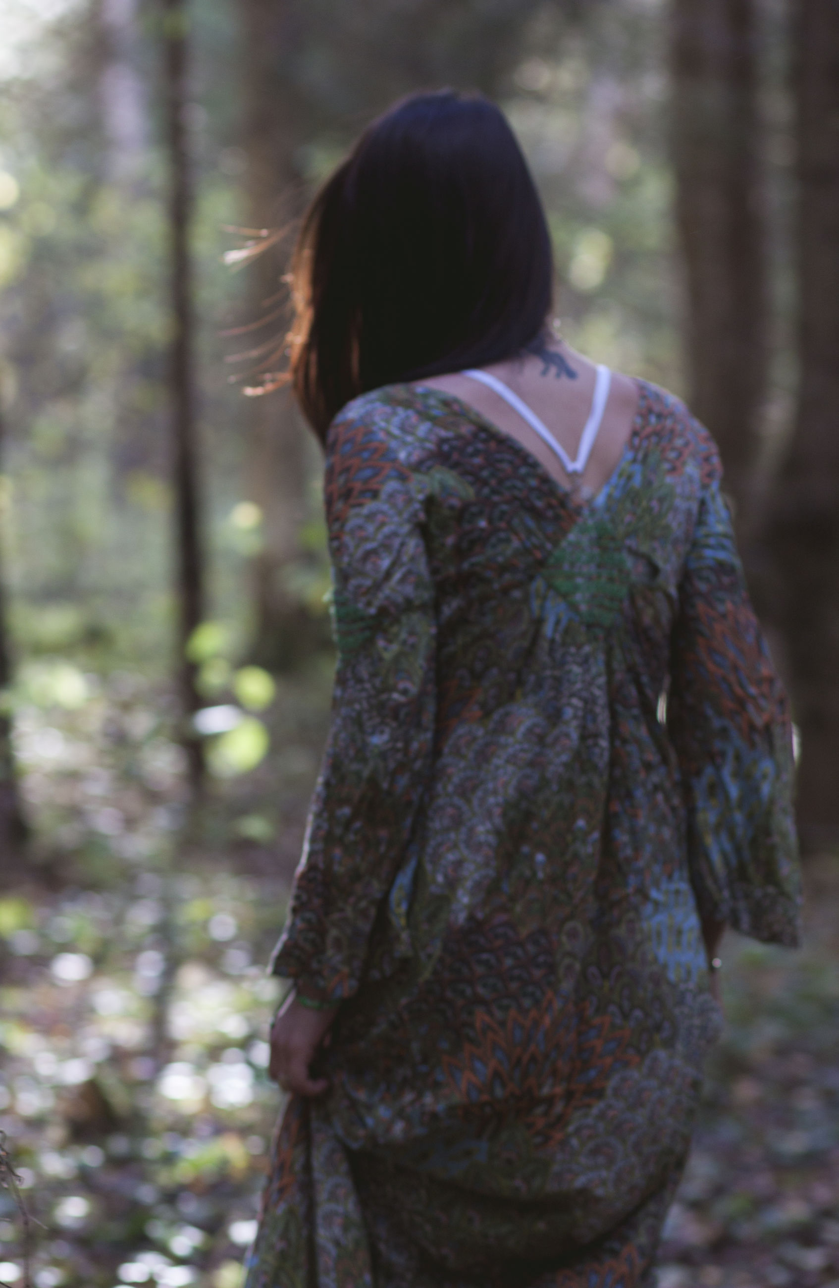 rear view, focus on foreground, person, casual clothing, tree trunk, looking, loneliness, tranquility, solitude