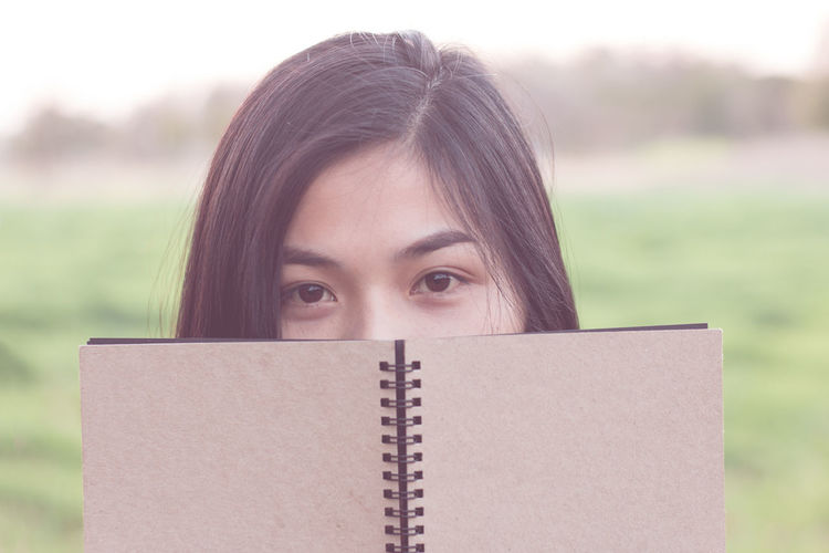 Close-up portrait of young woman reading book at park