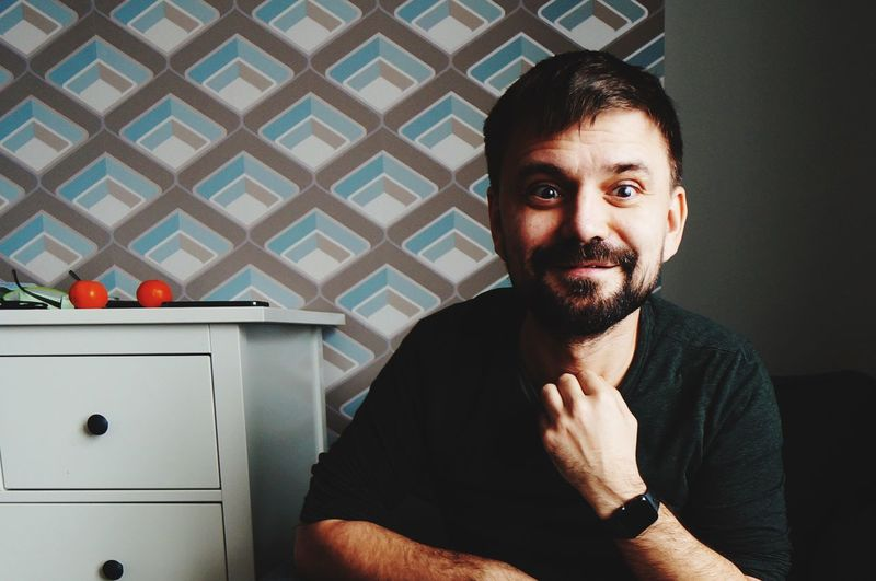 Portrait of man sitting against wall at home