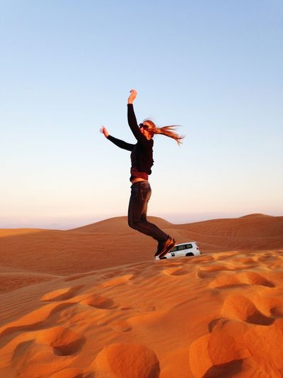 Side View Of Playful Woman Jumping At Desert Against Clear Blue Sky