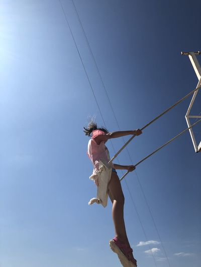 Low angle view of girl sitting on swing against blue sky