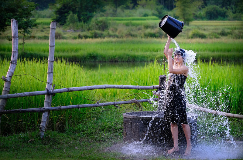 Full Length Of Woman Taking Bath By Well At Farm