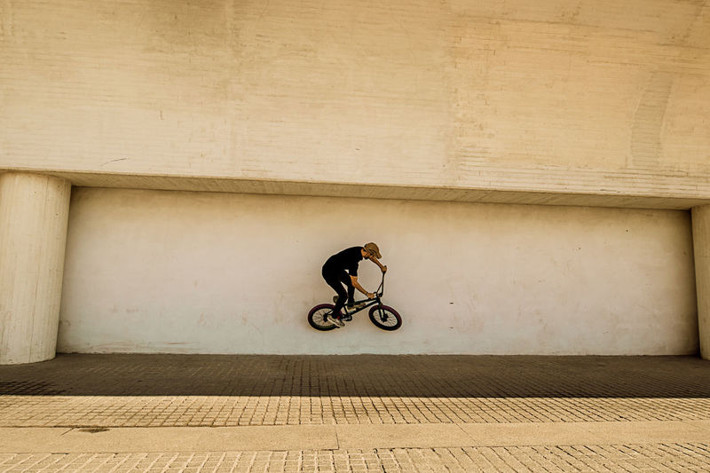 Man performing stunt with bicycle on wall