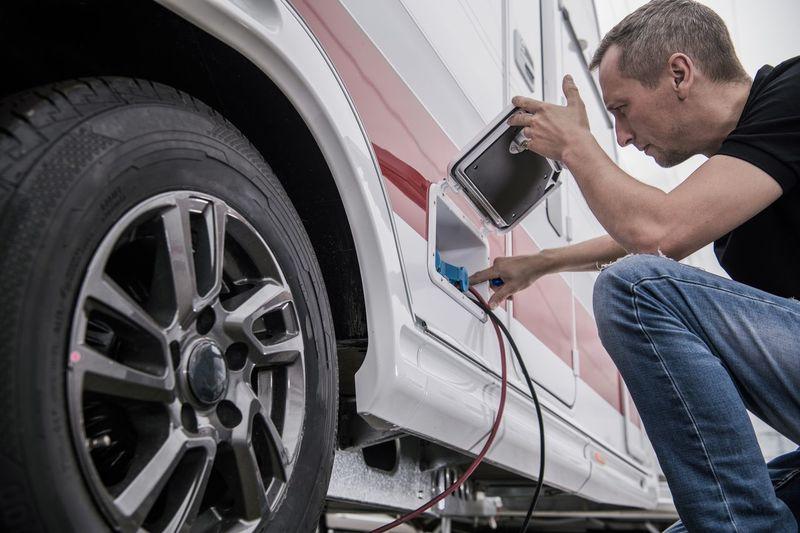 Low angle view of mechanic repairing vehicle