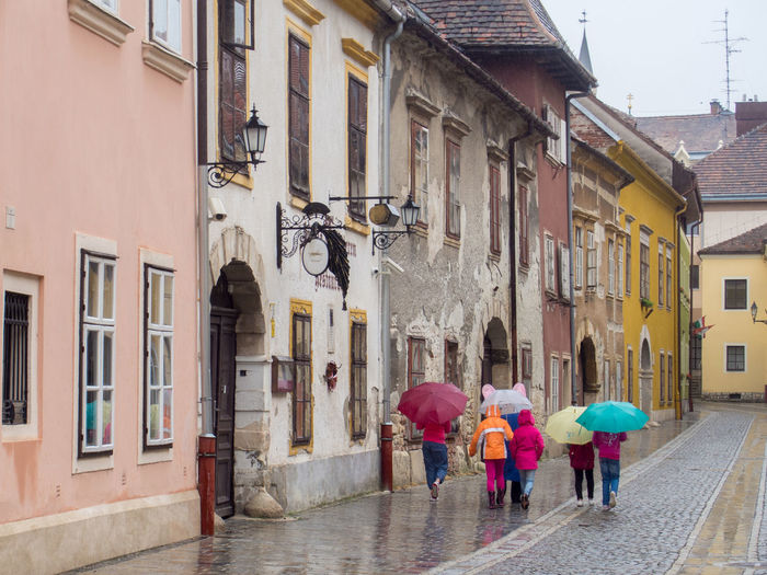 After Rain Building Exterior Children Cobblestone Cobblestone Streets Happy Happy People Hope Moody Weather Multicolors  Old And Young Old Buildings Old Houses Old Lamp Old Street Old Town Rainy Day Rear View Umbrella Umbrellas Variation Walking Wet Wet Day Youth