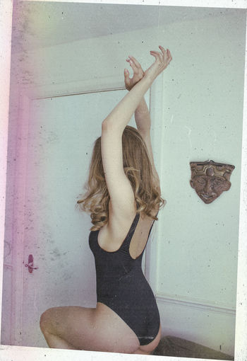 Woman with arms raised on wall