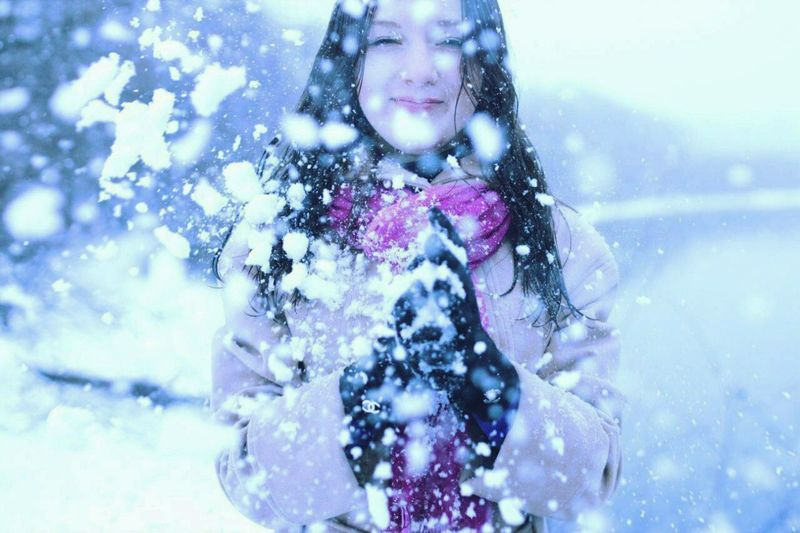 Happy woman holding snowflakes while snowing