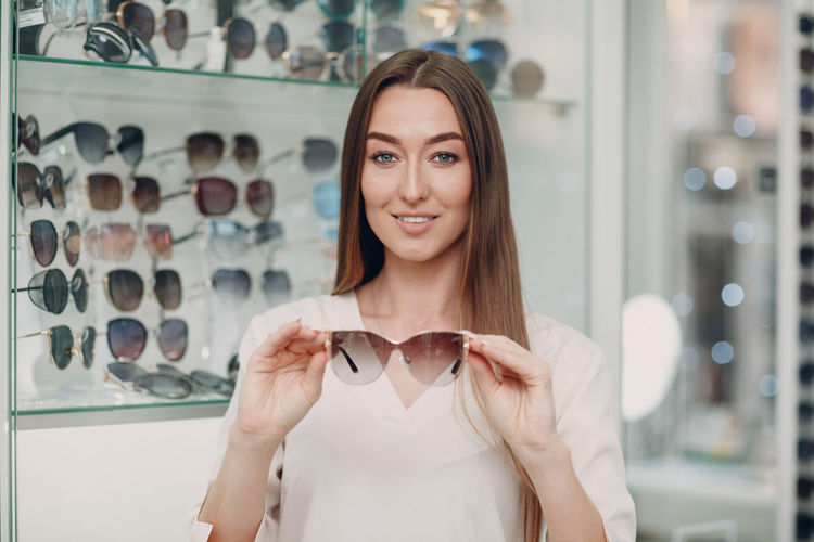 Portrait of smiling woman holding sunglasses at store